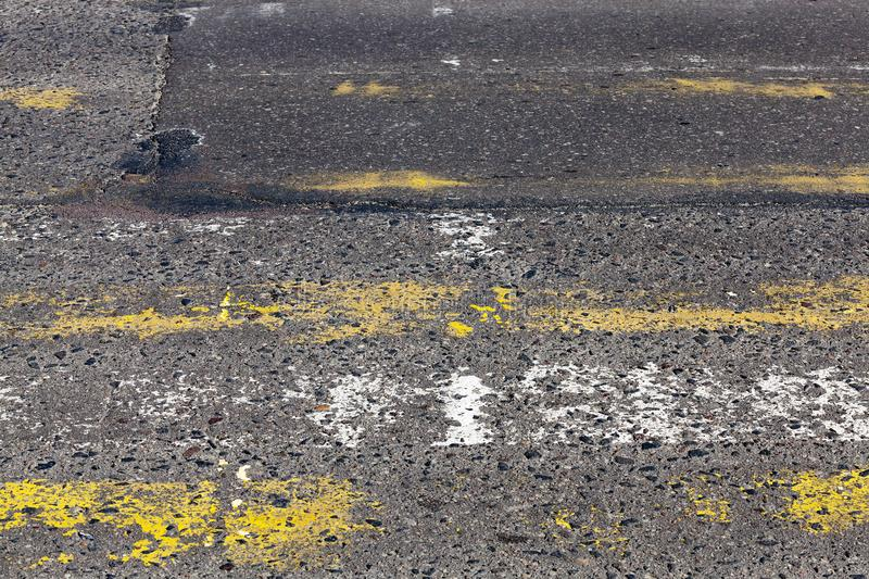 Road markings. Erased and worn road markings on the site of a pedestrian crossing through an asphalt road in the city, a closeup on a part of a roadway with a royalty free stock photos