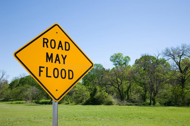 Road May Flood Sign Against A Blue Sky, Green Trees and Grass. A yellow road sign cautioning that the road may flood. It is set against a blue sky, green trees royalty free stock photo