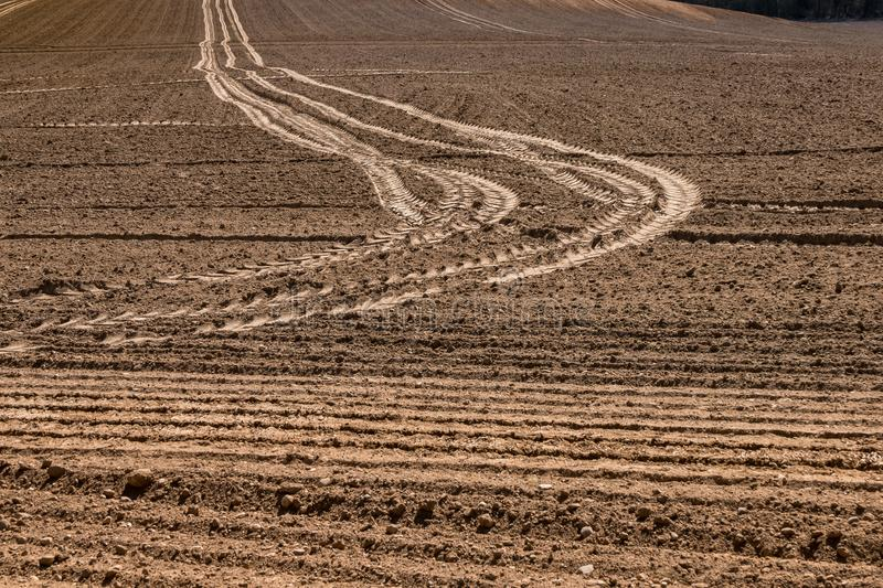 Road among meadow plowed spring fields with a lot of stones royalty free stock photos