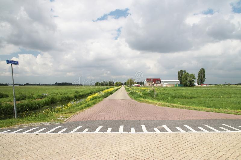 Road and meadows in the Zuidplaspolder at Nieuwerkerk aan den IJssel, one of the lowest parts of europ with 21 ft below sea level. Road and meadows in the royalty free stock images