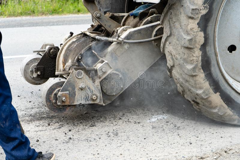 Road milling machine cuts the old asphalt. Road repair. Destruction of the road surface. The cutter cuts a layer of asphalt. royalty free stock photography