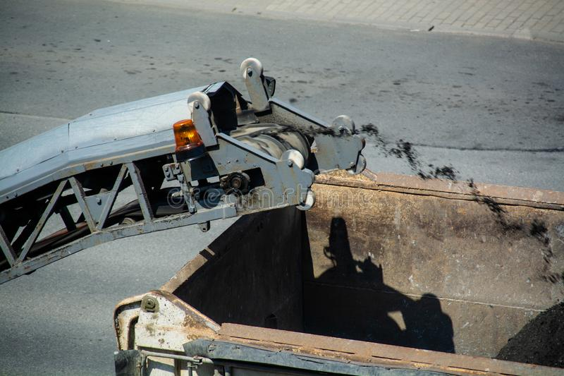 Road milling machine is loading the truck by asphalt powder. royalty free stock photos