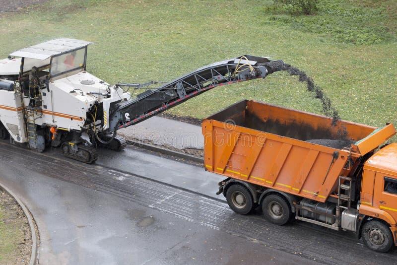 Road milling machine removes old asphalt stock images
