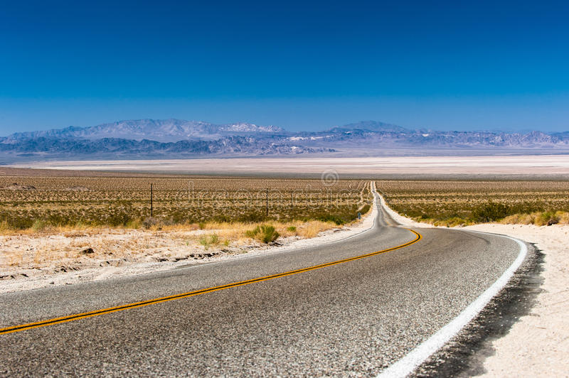 Road through the Mojave Desert. The Bristol Mountains and the Bristol Dry Lake in the back stock photo