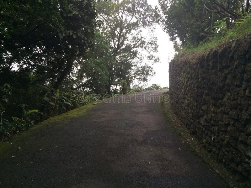 Road in mountains in Grecia, Costa Rica. Driveway road in mountains in Grecia, Costa Rica along an old stone rock wall royalty free stock image