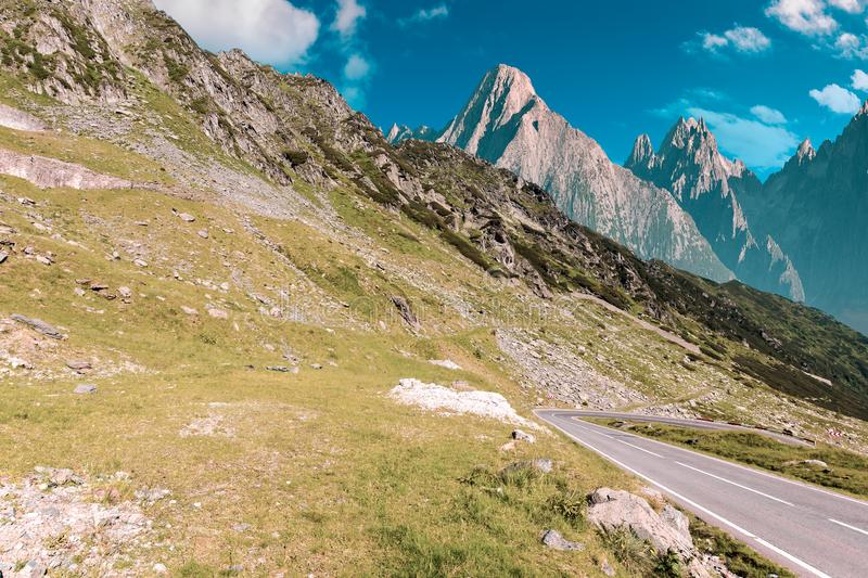 Road through mountains with rocky cliff royalty free stock photography