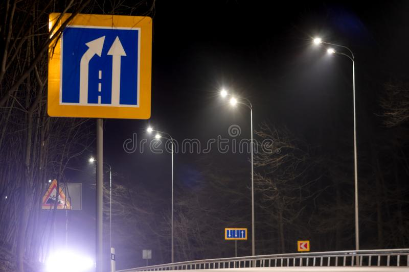 Road narrowing sign, street lighting, supports for ceilings with led lamps. concept of modernization and maintenance of lamps,. Place for text, night. energy royalty free stock images