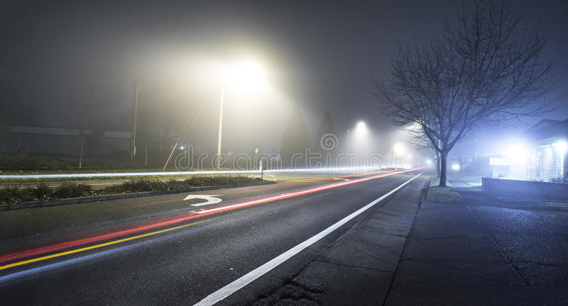 Road at night with fog and long exposure of car. Trail with sidewalk to the right royalty free stock image