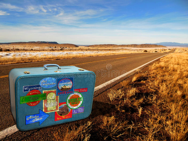 On the Road. Old 1950's suitcase with travel stickers sits on the side of an empty road awaiting the next adventure royalty free stock images