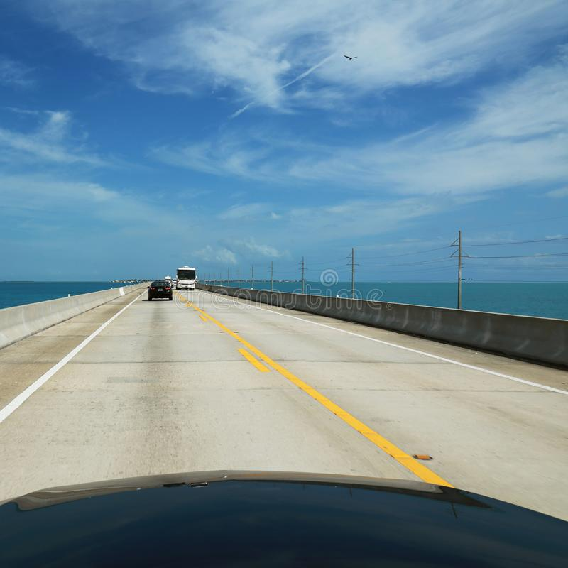Road passes through a beautiful wide ocean and goes beyond the h. Orizon, the background royalty free stock image