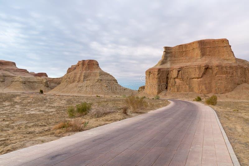 Road passes through the wind erosion landforms. World ghost town of karamay, xinjiang royalty free stock image