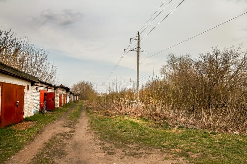 The road passing along the old car garages. Day stock images