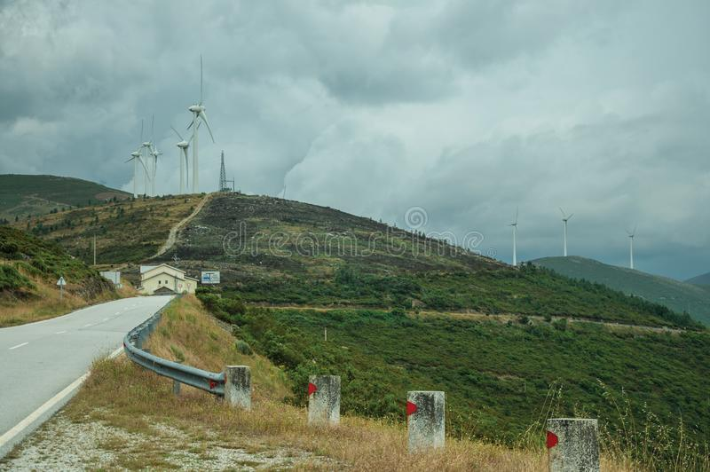 Road passing through hilly landscape with several wind turbines. Countryside road passing through hilly landscape with several wind turbines, in a cloudy day at stock image