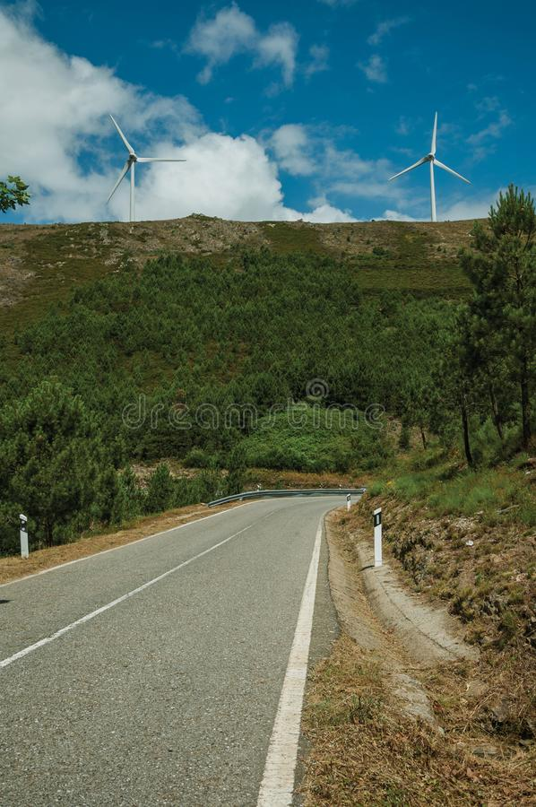 Road passing through hilly landscape with wind turbines. Countryside road passing through hilly landscape with several wind turbines, in a sunny day at Serra da stock photo