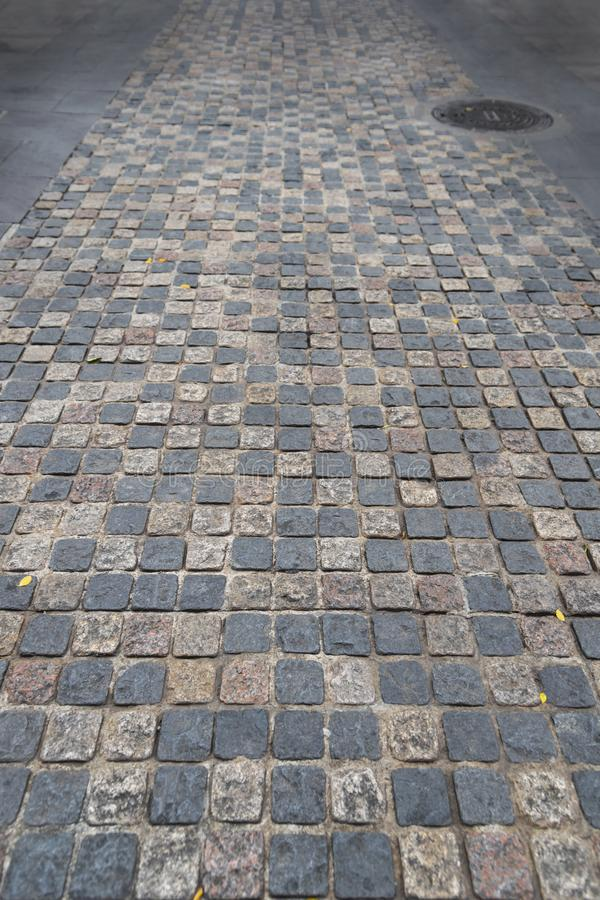 Road paved stones of a Brick Walkway,  background and pattern. Sidewalk, block, surface, outdoor, pebble, wallpaper, paving, street, cobblestone, square, floor royalty free stock photography