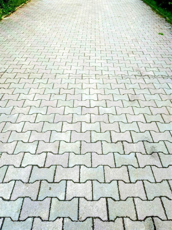 Road, pavement, built of stones. Gray color with geometric pattern. The road going away, built of stones of geometric pattern. On the sides is a green plant stock photography