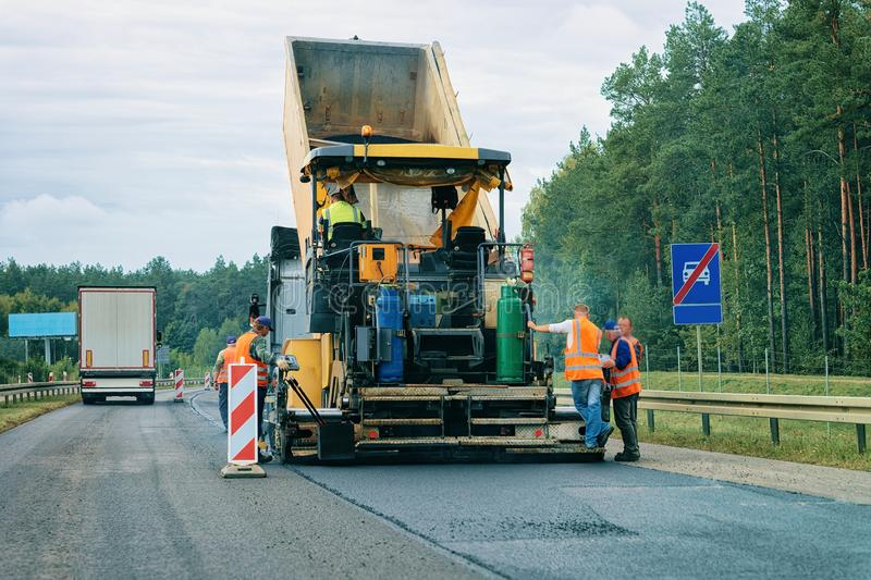 Road paving machine on road in Slovenia. Road paving machine on the road in Poland. Workers at paver finisher stock photos