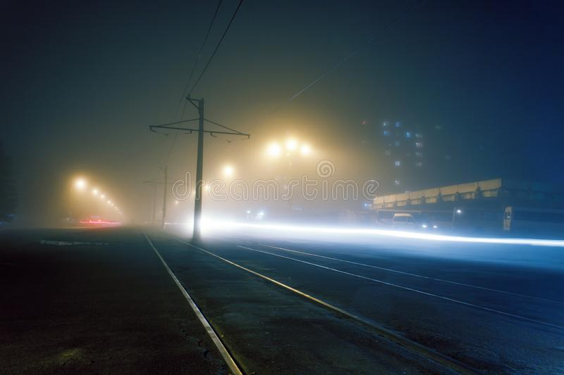 Road with poles with high-voltage wires and tram tracks or tram rails , evening fog on the streets, poles with high-voltage wires. Cityscape with freeze light royalty free stock images