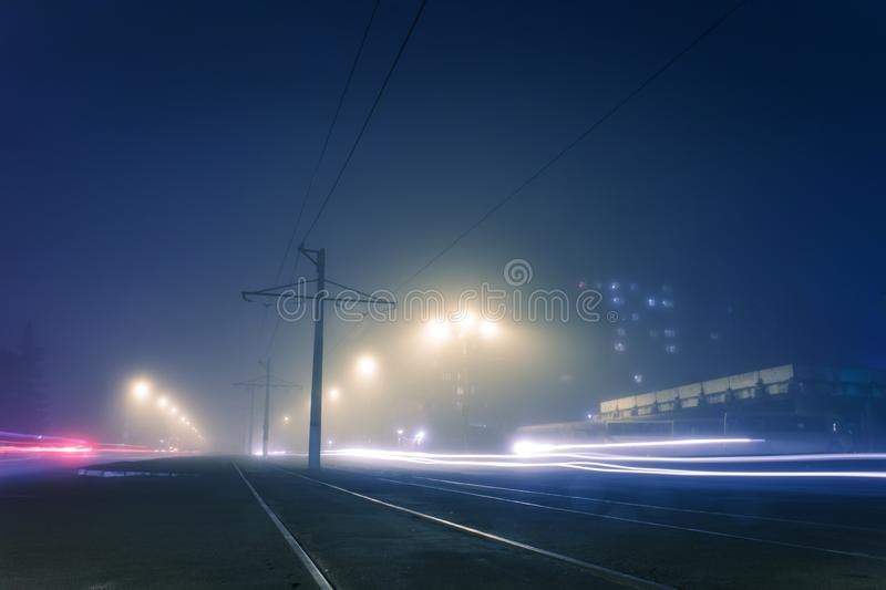 Road with poles with high-voltage wires and tram tracks or tram rails , evening fog on the streets, poles with high-voltage wires. Cityscape with freeze light stock photography