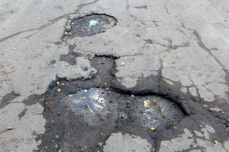 Road with potholes. Very bad quality road with potholes royalty free stock photography