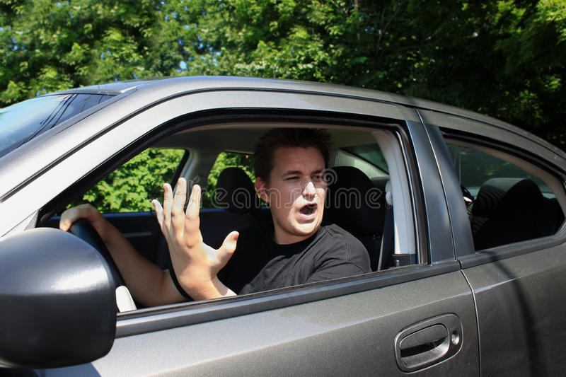 Road rage. Angry young male driver yelling and gesturing to someone stock photography