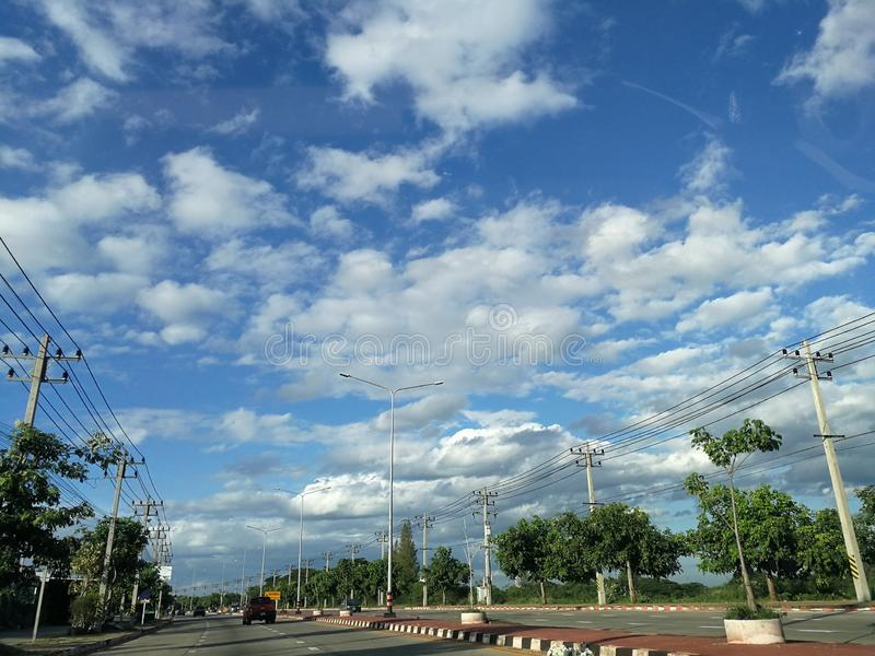 Road in Ratchaburi city, Thailand under the dramatic sky and scattered clouds stock photo
