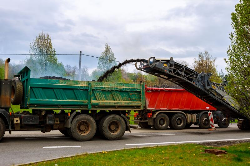 Road repair. Milling machine removes old asphalt from the road and transports it to a truck royalty free stock photo