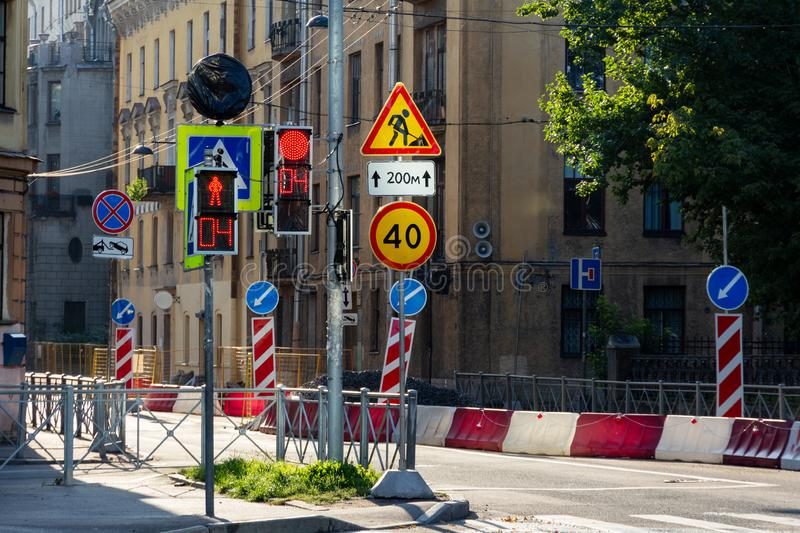 Road repair and old town crossroads with traffic lights and road signs on an early sunny summer morning. royalty free stock photo
