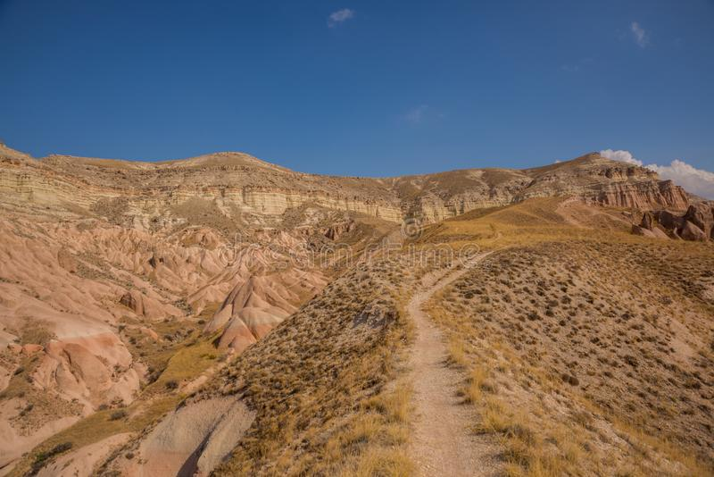 The road in the rocks in the Rose valley, Gulludere valley. In the distance White mountain, Aktepe hill. Cappadocia, Anatolia, royalty free stock photos
