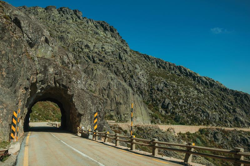 Road on rocky landscape passing through tunnel royalty free stock photography