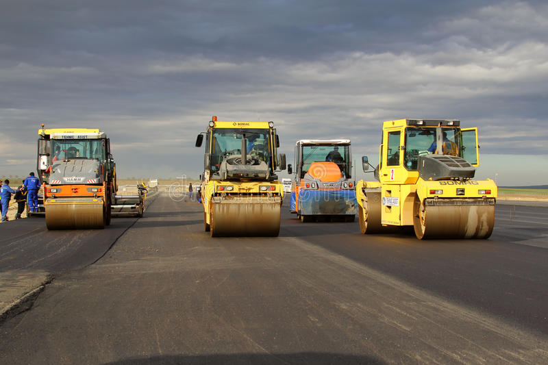 Road rollers leveling fresh asphalt pavement on a runway as part of the Danube Delta international airport expansion plan royalty free stock photos