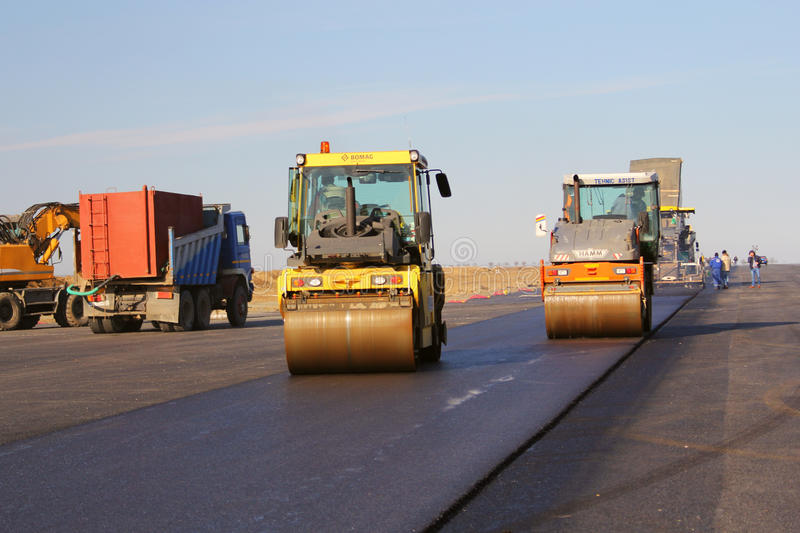 Road rollers leveling fresh asphalt pavement on a runway royalty free stock photography