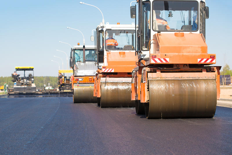 Road rollers machines compacting fresh asphalt royalty free stock images