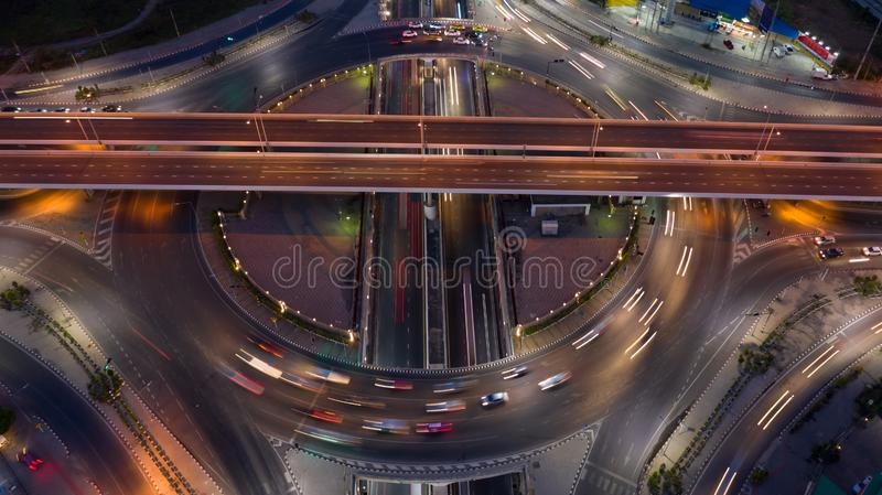 Road roundabout intersection in the city at night with vehicle car light movement, Aerial view.  stock images