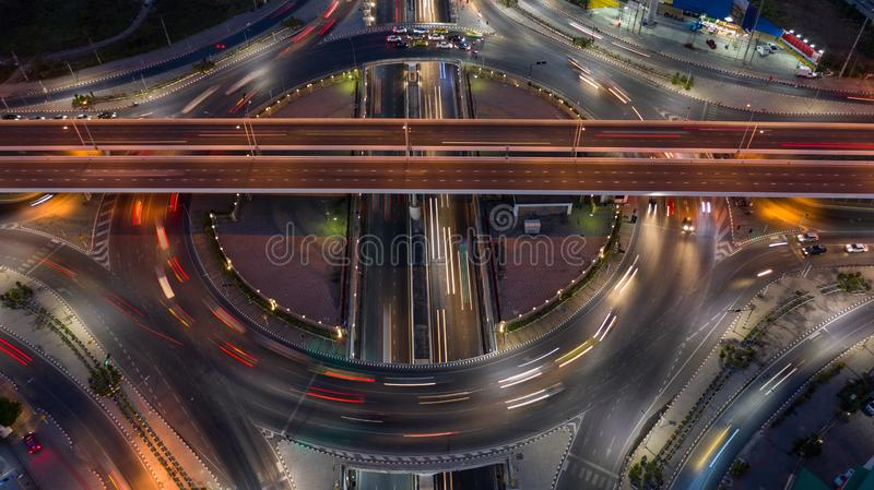 Road roundabout intersection in the city at night with vehicle car light movement, Aerial view.  royalty free stock photo