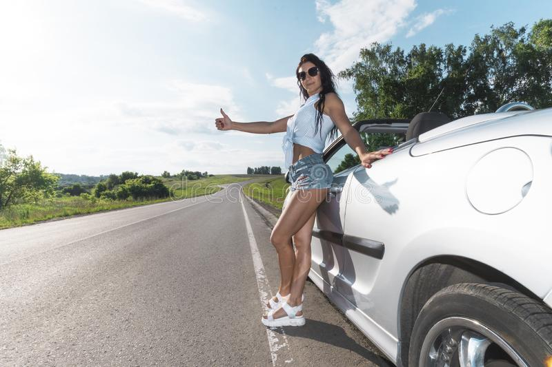 Road scene: sexy brunette girl standing near their broken car and hitchhiking. Rear view. ran out of gas. Problems with royalty free stock photos