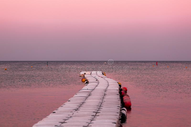 Road in the sea. Wooden Pier, leaving the horizon of the ocean. Water on the sunset. Landscape in natural lilac sun stock photo