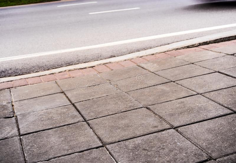 Road side pathway is paved with square blocks of concrete stock photography