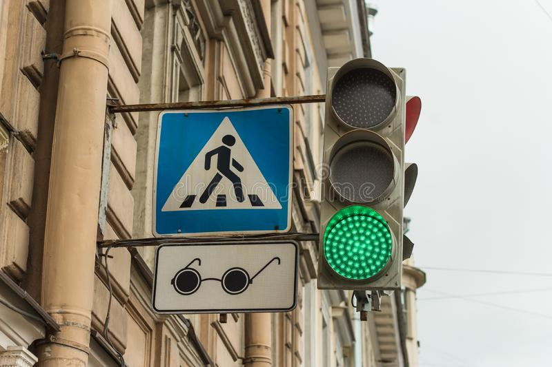 adjustable pedestrian crossing in blue with a badge for blind pedestrians in the form of black glasses stock photo