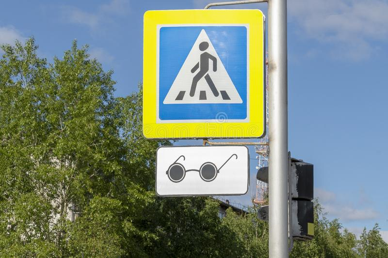 Road sign adjustable pedestrian crossing in blue with a badge for blind pedestrians in the form of black glasses. stock photos