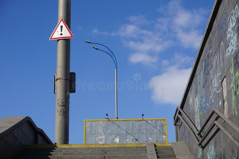 Road sign - black exclamation point in a red triangle hanging on a pole, warning about the danger. royalty free stock images