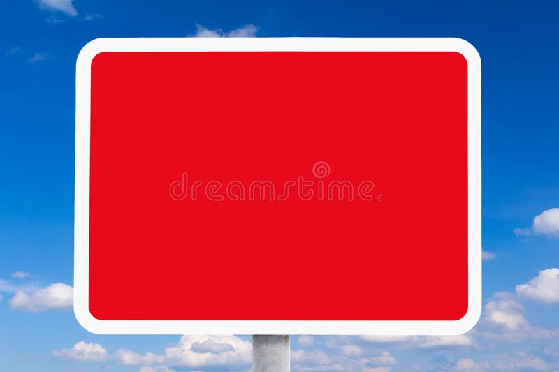 Road sign copy space danger background template. Blank or empty red and white british road sign in front of a blue sky with a few white clouds, symolising a stock image