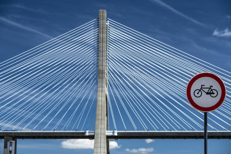 Road sign for cycling. No riding sign with bridge as backdrop in front of a blue sky with clouds stock photography