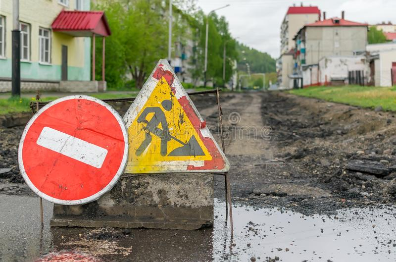 Road sign, detour, road repair on the background of the road and broken asphalt covering royalty free stock image