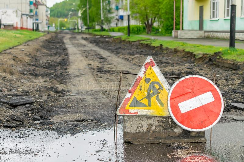 Road sign, detour, road repair on the background of the road and broken asphalt covering stock photo