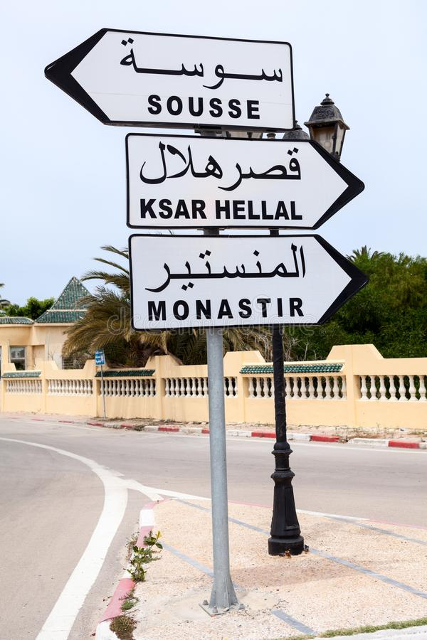 Road sign with directions to Monastir, Sousse and Ksar Hellal is in town of Tunisia. English and Arabic inscriptions. Africa. Road sign with directions to stock images