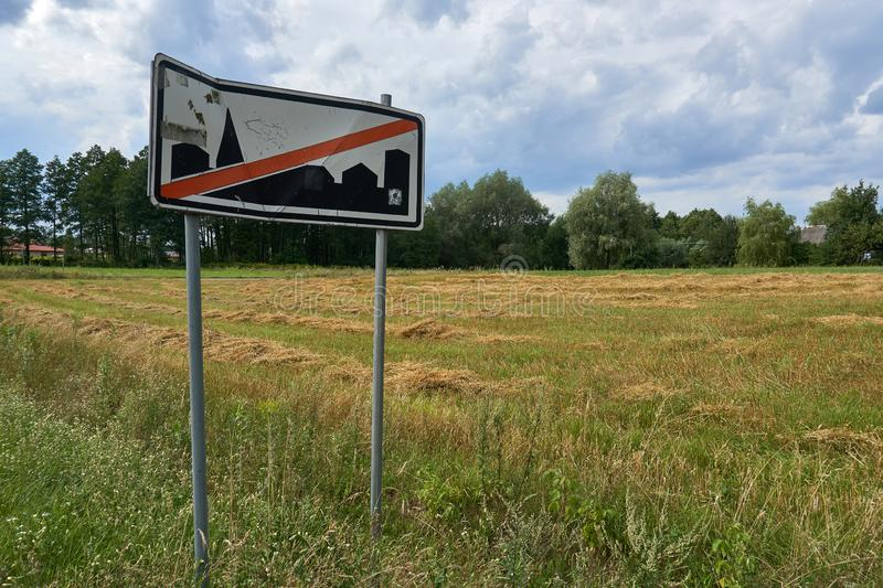 Road sign `End of built-up zone` on the background of a summer beautiful field in Poland stock photography