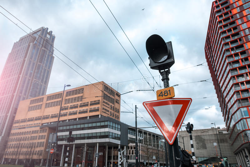 Road sign give way and a traffic light. Rotterdam Netherlands. Skyscrapers are on the background. stock photo