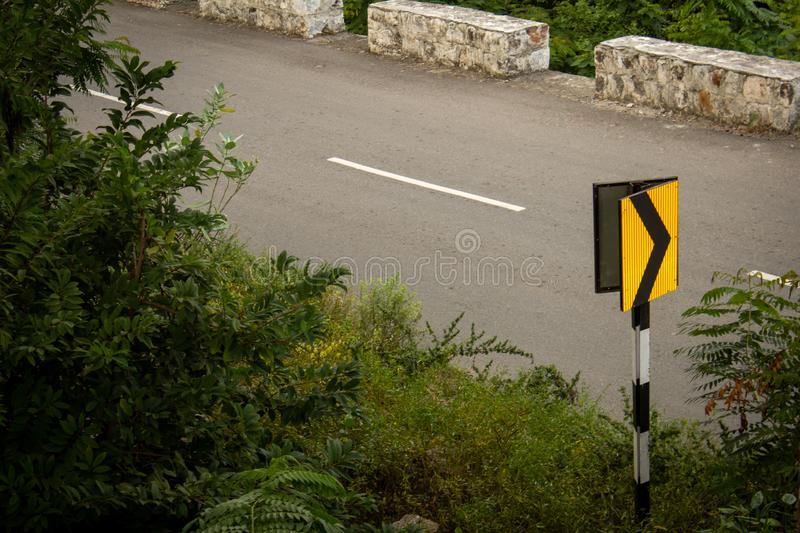 Road sign indicating turn ahead along the beautiful Ghat road in the mountain range of Salem, Tamil Nadu , India. Beautiful road going through the hills in stock photo