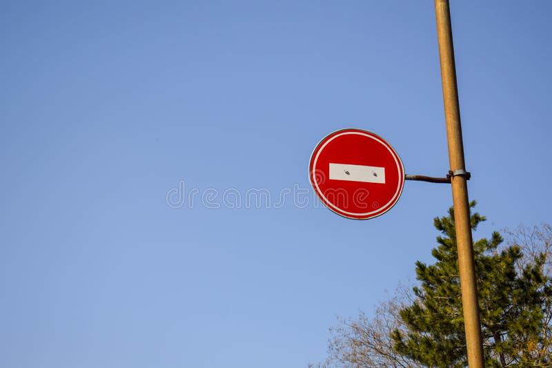Road sign No entry against the blue sky and trees stock image
